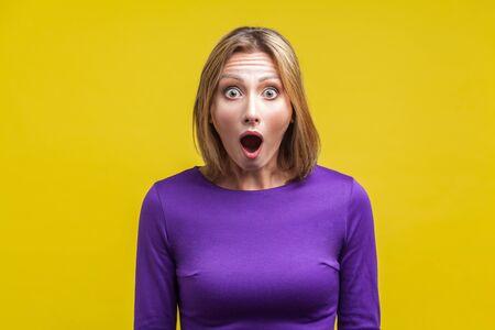 Wow, ich kann das nicht glauben! Porträt einer erstaunten Frau mit weit geöffnetem Mund in Erstaunen und großen Augen, die in die Kamera blicken, fassungsloses schockiertes Gesicht. Indoor-Studioaufnahme isoliert auf gelbem Hintergrund