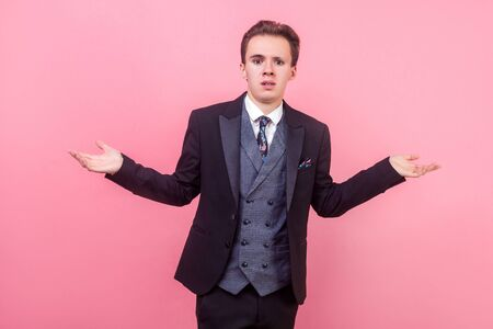 What do you want. Portrait of confused annoyed businessman in tuxedo standing with raised hands asking why what reason, indignant displeased expression. indoor studio shot isolated on pink background