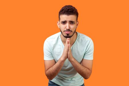 Please, I'm begging! Portrait of upset brunette man with beard in white t-shirt holding arms in prayer, asking help or forgiveness with imploring eyes. indoor studio shot isolated on orange background