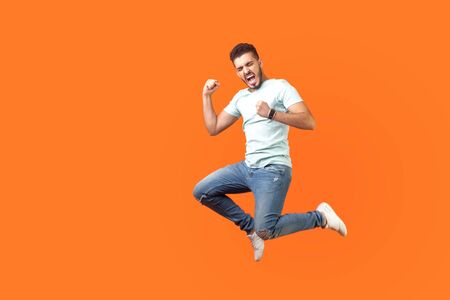 Side view of extremely happy man in white outfit jumping in air with raised arm gesturing yes i did it, I'm winner, screaming loud for joy feeling energetic and lively. isolated on orange background