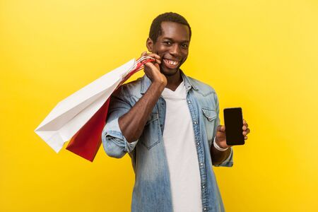 Mobile app for online shopping. Portrait of positive man with attractive toothy smile in denim casual shirt holding packages and showing smartphone. indoor studio shot isolated on yellow background Reklamní fotografie