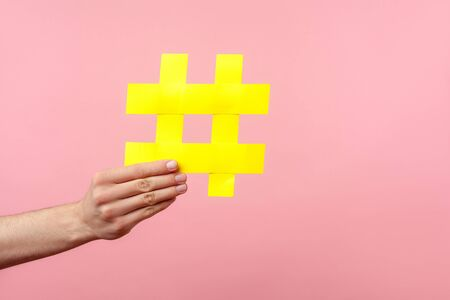 Closeup of male hand holding large yellow hashtag sign, concept of marketing and promotion in internet, followers in social media, trend content. indoor studio shot isolated on pink background Reklamní fotografie
