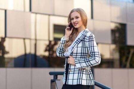 Portrait of stunning beautiful blond lady in stylish plaid jacket talking on cellphone, looking aside with charming toothy smile, successful rich businesswoman having conversation on phone, outdoor