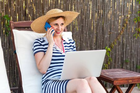 Portrait of beautiful satisfied young adult businesswoman in hat and dress sitting on sunbed with laptop and working online, making call with smartphone. Lifestyle concept, outdoor, summer vacation
