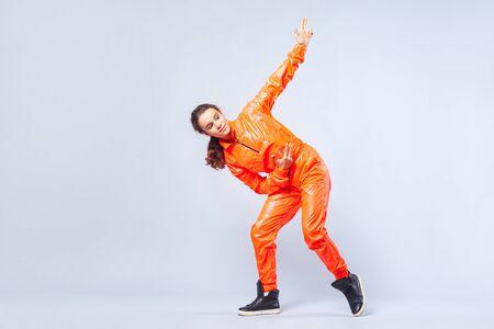 Ganzkörperporträt eines positiven, energetischen Teenagermädchens mit brünetten Haaren in leuchtend orangefarbenem Overall, das Hip-Hop tanzt und mit Fingerpistole nach oben zeigt, Hobbyaktivitäten. Studioaufnahme, weißer Hintergrund Standard-Bild