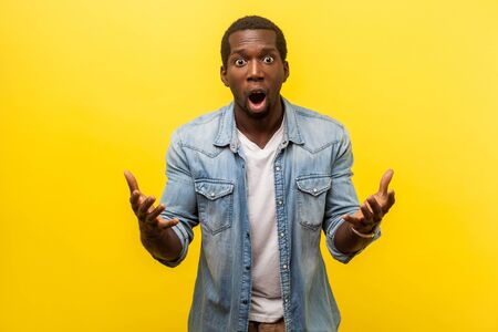 What do you want from me. Portrait of irritated angry man in denim shirt raising hands while disputing in conflict, looking annoyed and indignant. indoor studio shot isolated on yellow background Stock Photo