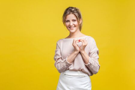 Portrait of pretty in love young woman with fair hair in casual beige blouse standing, showing heart sign with arms and looking at camera, romance. indoor studio shot isolated on yellow background