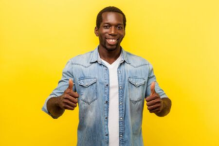 Thumbs up, excellent job! Portrait of enthusiastic handsome man in denim casual shirt with rolled up sleeves smiling and showing like gesture at camera. studio shot isolated on yellow background Stok Fotoğraf