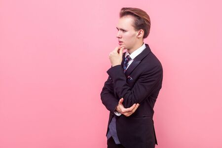 Let me think. Side view of pensive businessman in expensive suit and with stylish haircut touching his chin pondering business strategy with puzzled confused expression. indoor studio shot, copy space