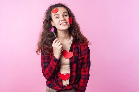 Valentinstag. Porträt eines charmanten Teenager-Mädchens mit lockigen brünetten Haaren und Herzaufklebern auf ihrem Gesicht und Kleidung, die rosa Papierlippen hält und in die Kamera lächelt. Innenstudioaufnahme, rosa Hintergrund