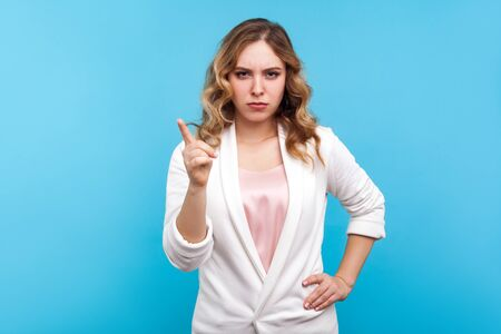 I told you! Portrait of bossy woman with wavy hair in white jacket frowning face and pointing finger up in warning gesture, teacher scolding with displeased expression. studio shot, blue background