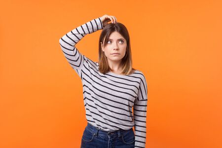 Need to think. Portrait of confused young woman with brown hair in long sleeve striped shirt standing, scratching head and looking up, solving problem. indoor studio shot isolated on orange background