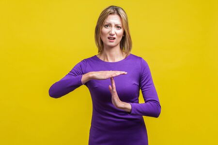 I need more time. Portrait of young woman in elegant tight purple dress standing with disgruntled face, showing time out gesture, asking pause. indoor studio shot isolated on yellow background Archivio Fotografico