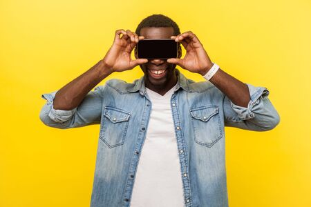 Portrait of positive cheerful man with toothy smile in denim casual shirt covering eyes with cellphone hiding his internet identity, anonymity concept. indoor studio shot isolated on yellow background Фото со стока