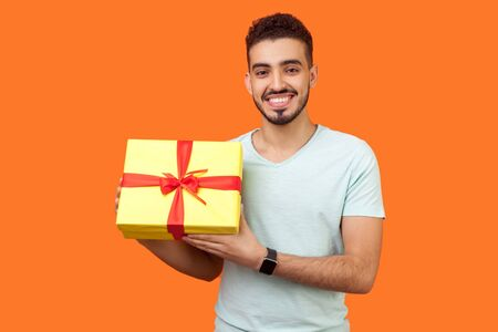 Portrait of positive young brunette man with beard in white t-shirt standing holding gift box and looking at camera with toothy smile, holiday present. indoor studio shot isolated on orange background
