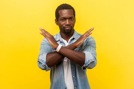 Never again. Portrait of absolutely convinced man in denim casual shirt standing crossing hands, showing x sign meaning stop, there is no way, finish. indoor studio shot isolated on yellow background