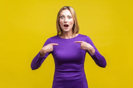 This is me! Portrait of amazed woman in elegant purple dress looking at camera with open mouth and pointing at herself, shocked about own success. indoor studio shot isolated on yellow background