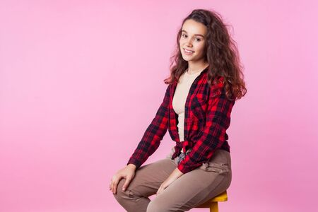 Portrait of trendy beautiful teenage girl with long curly brunette hair in plaid shirt sitting relaxed on chair and looking at camera with cute smile. indoor studio shot isolated on pink background