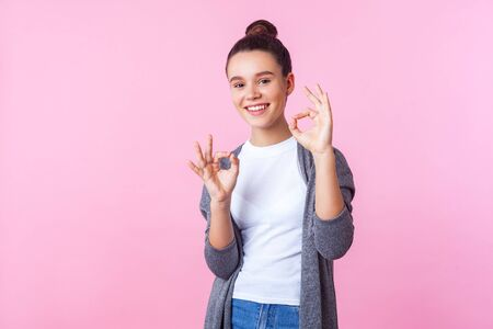 Im okay! Portrait of positive brunette teenage girl with bun hairstyle in casual pullover and T-shirt showing ok symbol, agree approve gesture, smiling kindly at camera. studio shot, pink background