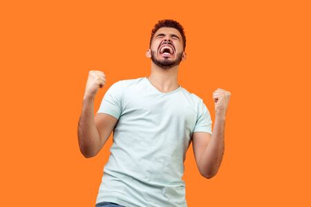 Bottom view of ecstatic motivated brunette man with beard in white t-shirt standing with raised fists and shouting for joy, winner excited for success. indoor studio shot isolated on orange background