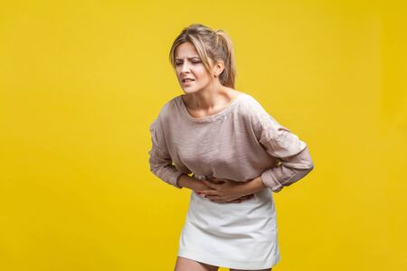 Portrait of unhealthy young woman with fair hair in casual beige blouse standing, touching stomach with arms, suffering pain, gastritis or indigestion. indoor studio shot isolated on yellow background