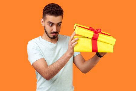 Portrait of calm cautious brunette man with beard in white t-shirt looking with interest inside gift box, carefully unpacking present, curious about whats inside. studio shot, orange background