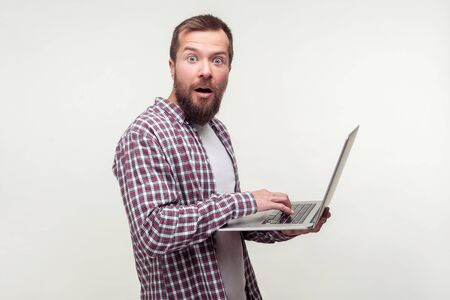 Portrait of amazed computer user, bearded man in casual plaid shirt standing with laptop and looking at camera with shocked expression, excited surprised about email news. studio shot white background