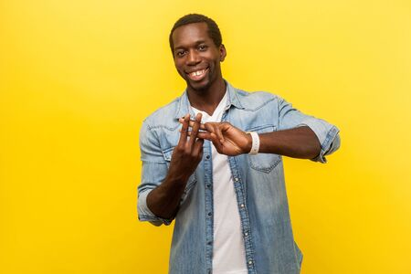 Hashtag symbol. Portrait of friendly joyful man in denim shirt making hash gesture with fingers and smiling, viral content concept, social media followers. studio shot isolated on yellow background