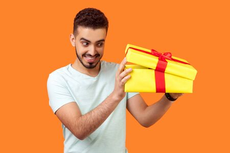 Whats in the box. Portrait of happy curious man with beard in t-shirt looking inside gift box, peeking with interest, unpacking long awaited present. indoor studio shot isolated on orange background