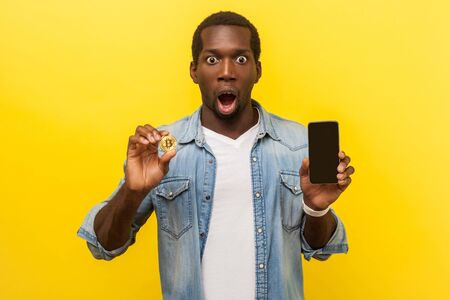Cryptocurrency mobile app. Portrait of excited man with astonished shocked face expression wearing casual shirt, holding cellphone and golden bitcoin. indoor studio shot isolated on yellow background