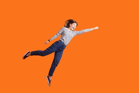 Superhero. Portrait of joyous pretty woman with brown hair in long sleeve shirt jumping high with one stretched arm, feeling to be superhero flying up. indoor studio shot isolated on orange background Фото со стока