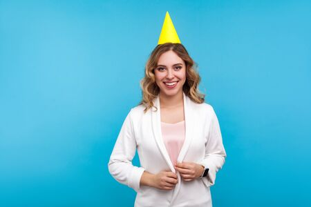 Portrait of pleased happy young woman with funny cone on head and in white jacket smiling at camera, enjoying birthday party, holiday celebration. indoor studio shot isolated on blue background