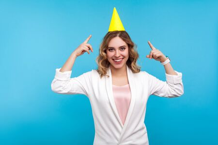 Portrait of happy young woman with funny cone on head and in white jacket pointing at hat and smiling at camera, enjoying birthday party, holiday celebration. studio shot isolated on blue background