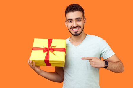 Look at my present! Portrait of happy brunette man with beard in white t-shirt standing pointing at wrapped box, satisfied with holiday gift, smiling. indoor studio shot isolated on orange background Reklamní fotografie