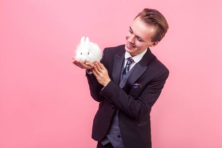 Love for pets. Portrait of pleased happy man in elegant suit and with stylish hairdo looking at white rabbit on his palm and smiling admiring cute bunny. indoor studio shot isolated on pink background