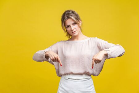Here and right now. Portrait of bossy woman with fair hair in casual beige blouse standing, pointing fingers down and looking at camera with demand. indoor studio shot isolated on yellow background