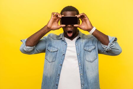 Portrait of stunned amazed man in denim shirt covering eyes with cellphone, hiding face to be anonymous, using gadget with wow shocked expression. indoor studio shot isolated on yellow background