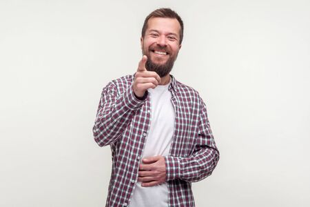 Haha, hey you! Portrait of joyful bearded man in plaid shirt pointing finger and holding belly, cant stop laughing, making fun towards friends with rude jokes. studio shot isolated, white background Reklamní fotografie
