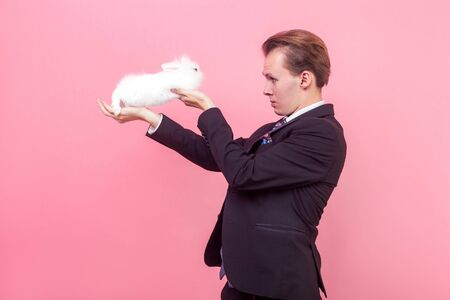 Side view of serious young man in elegant suit and with stylish hairdo holding white fluffy rabbit on raised hands and looking at bunny with curiosity. indoor studio shot isolated on pink background Reklamní fotografie