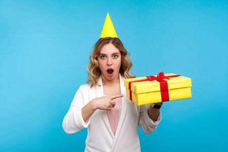 Portrait of surprised beautiful woman with birthday party cone on head and in white jacket pointing at present box and looking with amazement at camera. indoor studio shot isolated on blue background