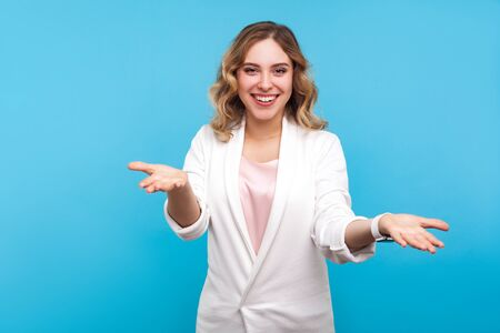Please take! Portrait of kind cheerful woman with wavy hair in white jacket raised hands as if sharing, giving for free, offering hugs with friendly generous face. indoor studio shot, blue background Фото со стока