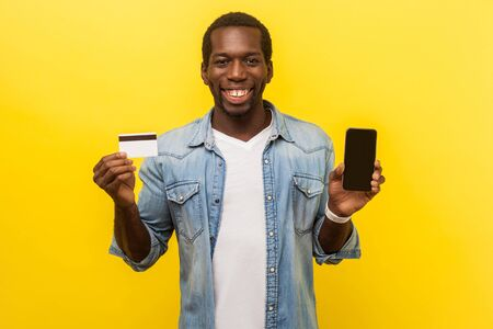 Online banking application. Portrait of happy positive man in denim casual shirt holding plastic bank card and cellphone, electronic money transfers. indoor studio shot isolated on yellow background