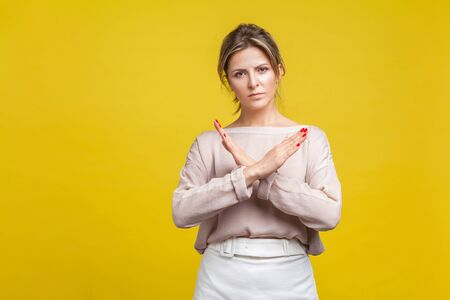No more, this is the end. Portrait of serious stubborn young woman with fair hair in casual blouse standing showing closed gesture with crossed hands. indoor studio shot isolated on yellow background