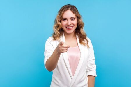 Hey you! Portrait of cheerful beautiful woman with wavy hair in white jacket pointing finger at camera with smiling happy expression, making choice. indoor studio shot isolated on blue background Фото со стока