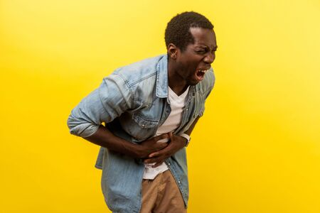 Portrait of sick man in denim shirt hunching and grimacing from strong abdominal pain, holding hands on belly, having gastritis or appendicitis symptoms. studio shot isolated on yellow background
