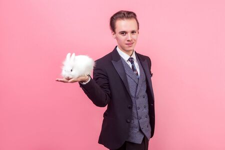 Pet care. Portrait of young handsome positive man in elegant suit with stylish hairdo standing holding cute bunny rabbit on his palm, smiling at camera. indoor studio shot isolated on pink background