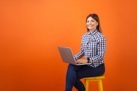 Portrait of happy freelancer, young woman with brown hair in checkered casual shirt and denim sitting, working on laptop and smiling at camera. indoor studio shot isolated on orange background