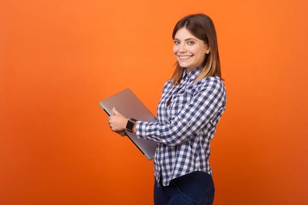 Portrait of fancy brunette woman with charming smile in checkered casual shirt standing holding closed laptop and looking at camera with toothy smile. indoor studio shot isolated on orange background Фото со стока