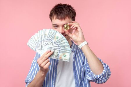 Portrait of successful young brown-haired man with small beard and mustache in casual striped shirt covering one eye with bitcoin and holding dollars. indoor studio shot isolated on pink background