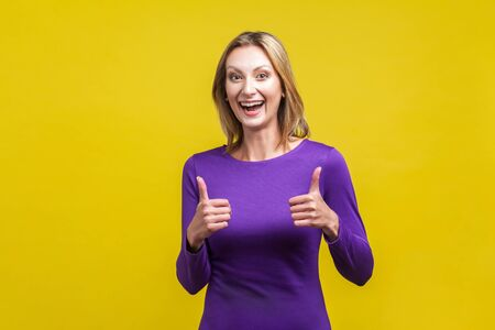 Good job! Portrait of extremely happy woman in tight purple dress showing thumbs up and smiling broadly at camera, overjoyed excited expression. indoor studio shot isolated on yellow background Фото со стока